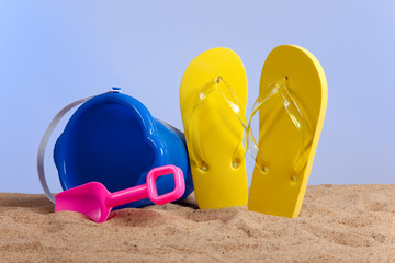 Bucket, shovel and flipflops on the beach