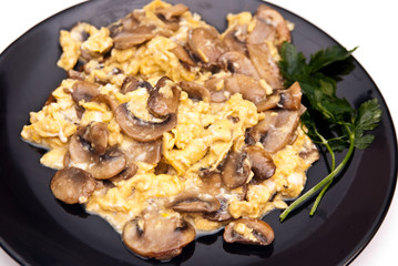 scrambled eggs with champignon mushrooms on frying pan