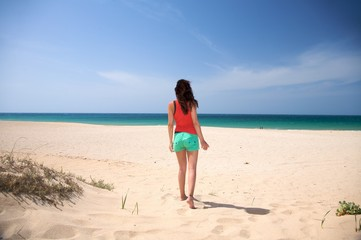 brown haired woman walking on the sand