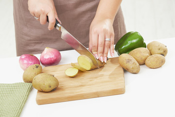 Female hand chopping potatoe