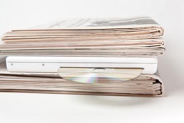 Stapel Zeitungen mit Laptop und CD dazwischen