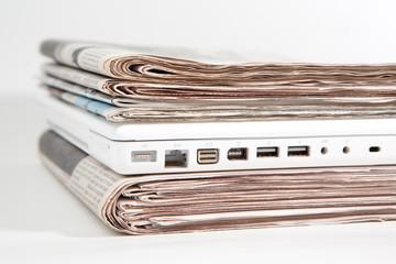 Stapel Zeitungen mit Laptop dazwischen