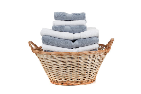 Wicker laundry basket full of white and gray towels