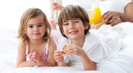 Smiling siblings having breakfast