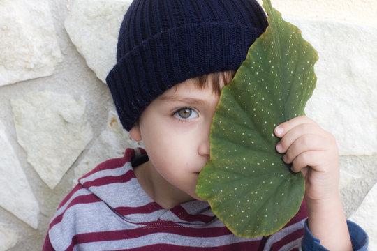 bambino con foglia sul viso