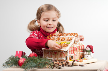 Little girl decorating Christmas cookies house