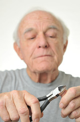 Elderly man cuts his fingernail with plyers