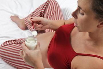 Pregnant woman eating a yogurt