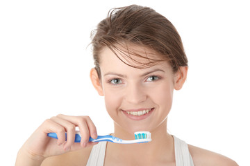Young girl brushing her teeth happily