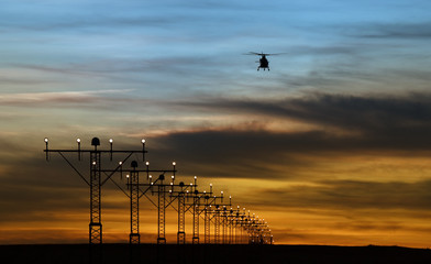 runway lights and silhouette of a helicopter