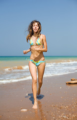 Attractive girl running along the beach
