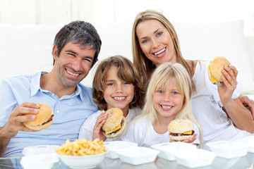 Happy family eating hamburgers sitting on the floor