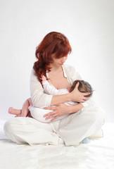 Mother feeding her baby. Cross-cradle