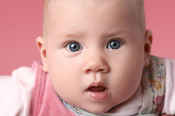 Little cute surprised child. Close-up portrait on pink backgroun
