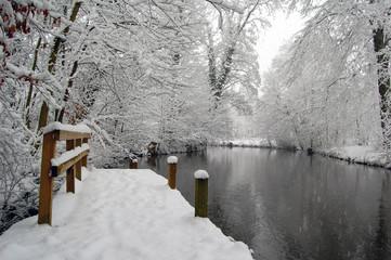 Ponton enneigé au bord d'une rivière gelée en Scandinavie