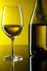 Glass and bottle of white wine.