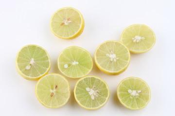 Many half-cut lemons on white background