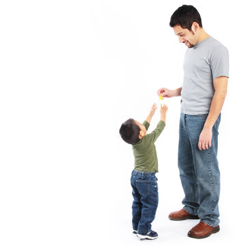 Happy father giving food to toddler son