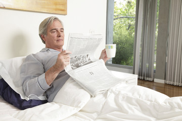 Senior man drinking coffee and reading newspaper