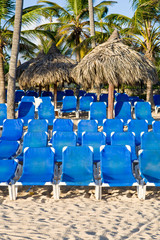 Blue plastic Lounges on white sand beach