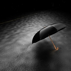 At night, the rain falls on a black umbrella lying on the road