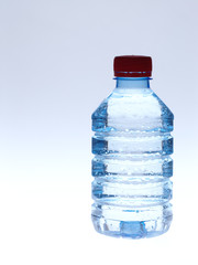 Cold spring water in the bottle with water droplets