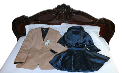 Men's suite and women's dress on the bed with dollar bills