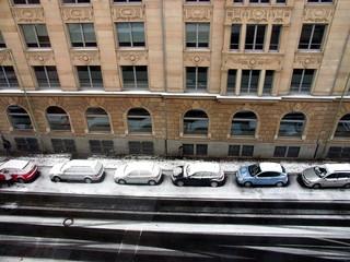 Zugeschneite Auto im Winter vor einer alten Fassade aus Sandstein in der Kaiserstraße in Offenbach am Main