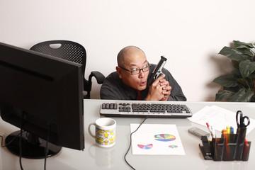 A businessman hiding behind his desk with a gun.