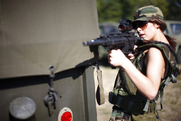young female soldier aiming an assault rifle