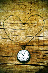 pocket watch heart  on a wood background