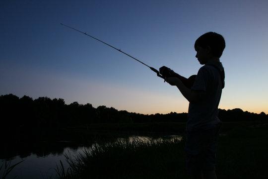 boy fishing in silhouette