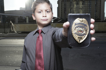 Young detective showing his badge