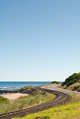 Coastal rail line by beach and ocean