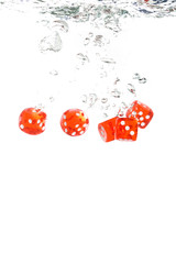 Red transparent dice falling into the clear water