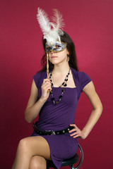 Beautiful russian girl in dress with mask sit at chair