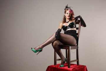 woman in a burlesque outfit sitting on a chair
