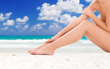 woman legs over tropical beach background
