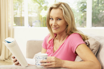 Woman Reading Book With Drink At Home