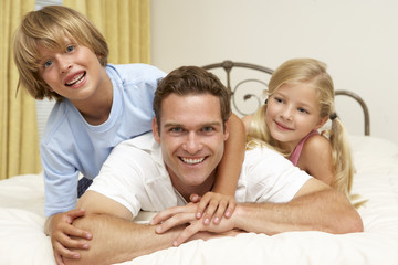 Father And Children Relaxing On Bed At Home