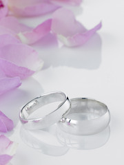 Silver Wedding Rings Resting Next To Flower Petals