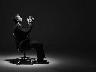 Businessman Sitting In Spotlight