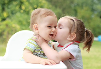 Young girl giving kiss for her young brother