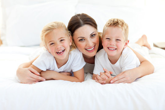 Laughing children playing with their mother lying on a bed