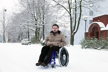 young man in wheelchair at the park on a cold winterday