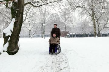 junger Rollstuhlfahrer mit Freund im Park