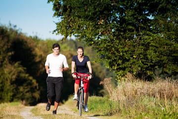 Sport-Paar joggt und fährt Farrad