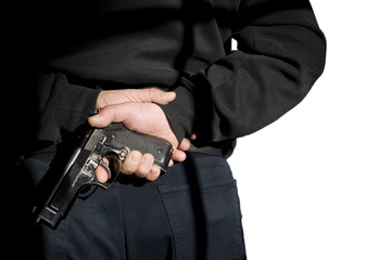 Terrorism.Person holds(hide) a handgun behind a back.