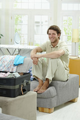Young man packing for vacation