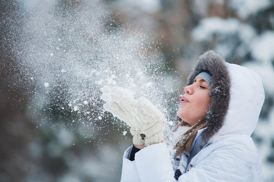 Beautiful woman blowing in the snow